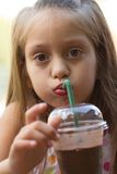 Funny little girl drinks milkshake Stock Photography