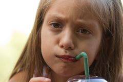 Funny little girl drinks milkshake Stock Photos