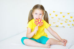 Funny little girl eating big sugar lollipop. Funny child with candy lollipop, happy little girl eating big sugar lollipop, kid eat sweets Stock Image