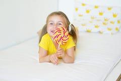 Funny little girl eating big sugar lollipop. Funny child with candy lollipop, happy little girl eating big sugar lollipop, kid eat sweets Royalty Free Stock Image