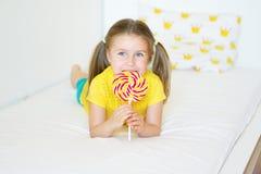 Funny little girl eating big sugar lollipop. Funny child with candy lollipop, happy little girl eating big sugar lollipop, kid eat sweets Stock Photos