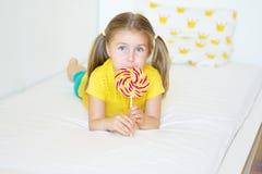Funny little girl eating big sugar lollipop. Funny child with candy lollipop, happy little girl eating big sugar lollipop, kid eat sweets Stock Photo