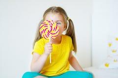 Funny little girl eating big sugar lollipop. Funny child with candy lollipop, happy little girl eating big sugar lollipop, kid eat sweets Royalty Free Stock Photo
