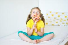 Funny little girl eating big sugar lollipop. Funny child with candy lollipop, happy little girl eating big sugar lollipop, kid eat sweets Stock Photography