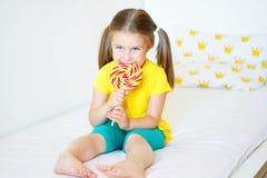 Funny little girl eating big sugar lollipop. At home Stock Image
