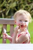 Funny little girl eating grilled meat from spoon Stock Photos