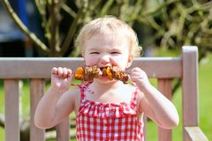 Funny little girl eating grilled meat from spoon Royalty Free Stock Photo