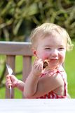 Funny little girl eating grilled meat from spoon Royalty Free Stock Photos