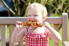 Funny little girl eating grilled meat from spoon. Funny child, adorable blonde toddler girl in red dress messy around mouth eating delicious meat made on bbq Stock Photo