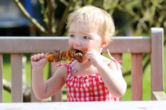 Funny little girl eating grilled meat from spoon Royalty Free Stock Photography