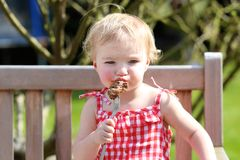 Funny little girl eating grilled meat from spoon. Funny child, adorable blonde toddler girl in red dress messy around mouth eating delicious meat made on bbq Royalty Free Stock Photography