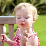 Funny little girl eating grilled meat from spoon Royalty Free Stock Images