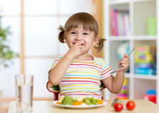 Funny little girl eating healthy food in kindergarten. Funny kid girl eating healthy food in kindergarten Royalty Free Stock Photography