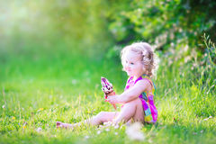 Funny little girl eating ice cream in the garden Stock Photos