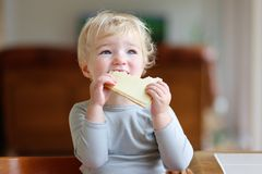 Funny little girl eating sandwich at home Royalty Free Stock Photos