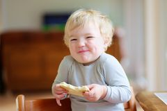 Funny little girl eating sandwich at home Stock Images