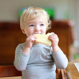 Funny little girl eating sandwich at home stock photos