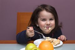 funny little girl eating. She is sitting at the table royalty free stock photo