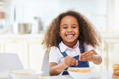 Funny little girl eating spaghetti Stock Photography