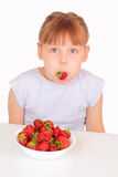 Funny little girl eating strawberries Stock Images