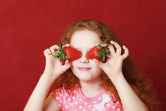 Funny little girl is eating strawberry Stock Image