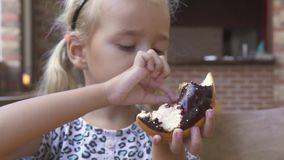 Funny little girl eating sweet chocolate donut at table in cafe. Face cute blond girl biting chocolate doughnut at. Dessert in restaurant stock video footage