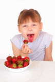 Funny little girl eating tasty strawberries Royalty Free Stock Photos