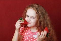 Funny little girl is eating tasty strawberry Stock Photo