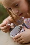 Funny little girl eats ice-cream Royalty Free Stock Photo