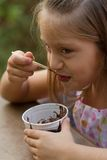 Funny little girl eats ice-cream Stock Photos