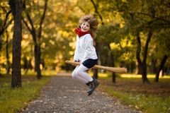 Funny little girl flies on broom in autumn. Park royalty free stock photography
