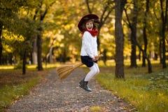Funny little girl flies on broom in autumn. Park stock photos