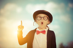 Funny little girl in glasses, bow tie and bowler hat. Royalty Free Stock Photo
