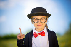 Funny little girl in glasses, bow tie and bowler hat. Royalty Free Stock Photos