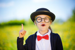 Funny little girl in glasses, bow tie and bowler hat. Stock Photo