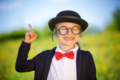 Funny little girl in glasses, bow tie and bowler hat. Royalty Free Stock Photography