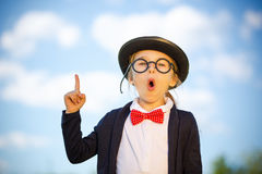 Funny little girl in glasses, bow tie and bowler hat. Funny little girl in glasses, bow tie and bowler hat pointing finger up. Retro stile Royalty Free Stock Photography