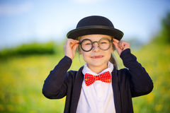 Funny little girl in glasses, bow tie and bowler hat. Stock Photos
