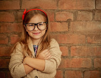 Funny little girl with glasses. On brick wall background stock photo