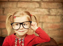 Funny little girl with glasses. On brick wall background royalty free stock photo