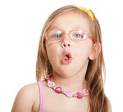 Funny little girl in glasses eating bread doing fun isolated. Funny little girl in glasses eating a bread doing fun isolated on white background. Happy childhood royalty free stock photography