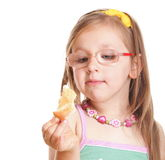 Funny little girl in glasses eating bread doing fun isolated Stock Images