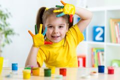 Funny little girl with hands painted in colorful Royalty Free Stock Photography