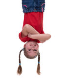 Funny little girl hanging upside down. On white Stock Photo