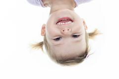 Funny little girl hanging upside down on white Royalty Free Stock Photo