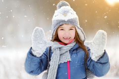 Funny little girl having fun in beautiful winter park during snowfall Stock Photos