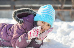 Funny little girl having fun in beautiful winter park during snowfall Royalty Free Stock Image