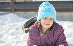 Funny little girl having fun in beautiful winter park during snowfall Stock Image