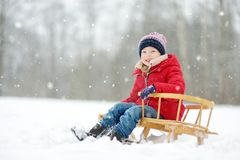 Funny little girl having fun with a sleigh in beautiful winter park. Cute child playing in a snow. royalty free stock photo