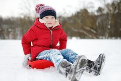 Funny little girl having fun with a sleigh in beautiful winter park. Cute child playing in a snow. royalty free stock images